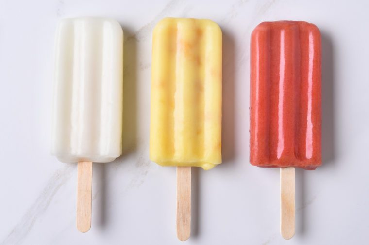 top view of three different ice pops on a marble counter top. Red, yellow and white fruit flavored frozen treats.