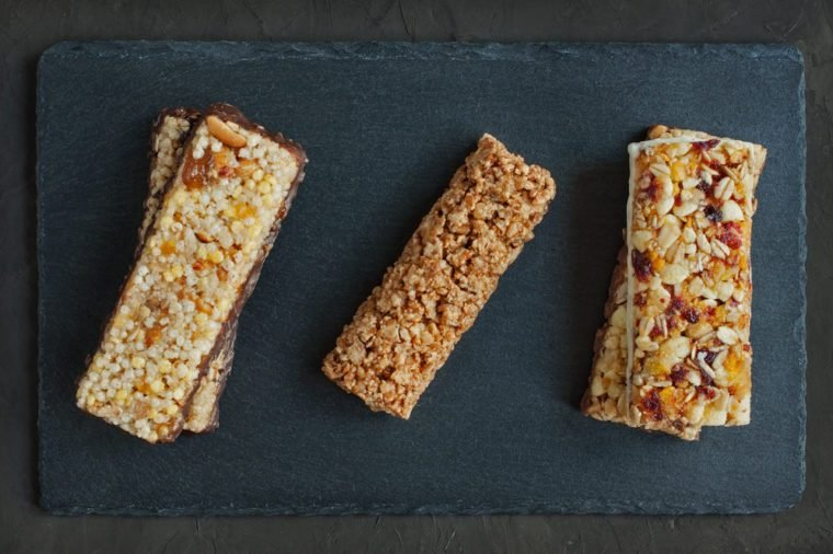 Various of granola bars on black slate background. Top view.