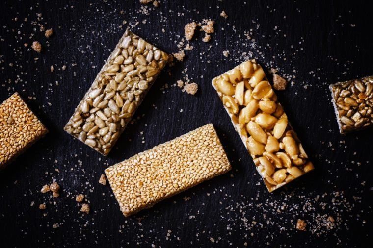 Sesame seeds, sunflower and peanuts in caramel, dark food background, selective focus