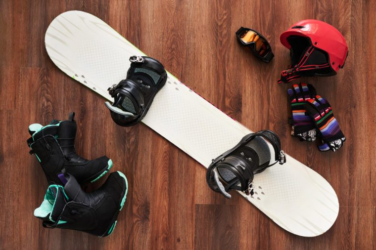 set of snowboard equipment boots, helmet, gloves and mask on a wooden floor