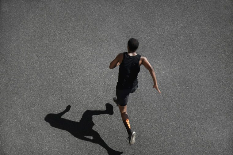 Top view of running man sprinting for success on run. African muscular runner or jogger dressed in black outfit, training at fast speed on black asphalt. Fit sport model exercising sprint outdoors