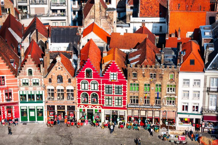 Famous old colorful buildings at Market square in Bruges, Belgium. Popular Flemish city with almost intact medieval architecture. Motion blurred people