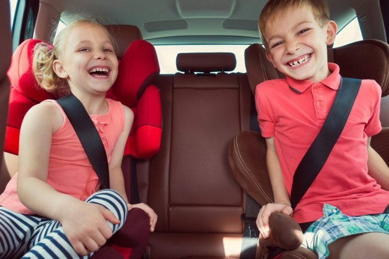 Happy kids, adorable girl with her brother sitting together in modern car locked with safety belts enjoying family vacation trip on summer weekend