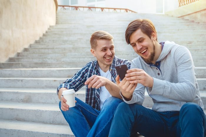 Two young men sitting on the steps and laughing, looking at the phone