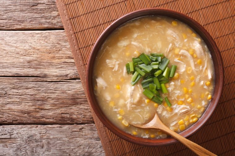 Chinese corn and chicken soup in a bowl macro on the table. horizontal view from above