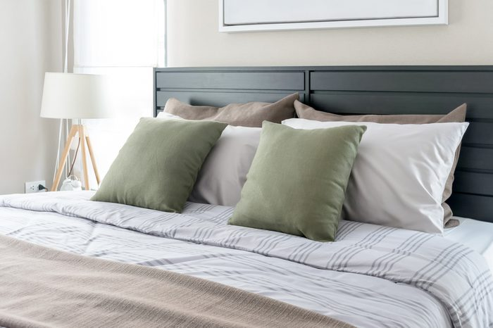 modern bedroom with green pillows on bed