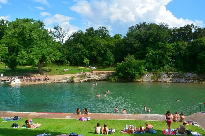 Barton Springs Pool in Austin, TX, with people.