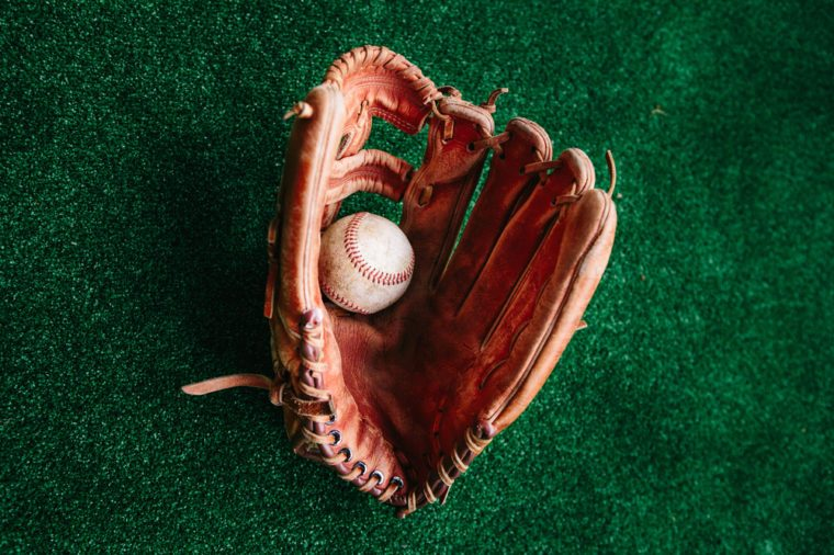 The old leather glove of the baseball catcher and the ball