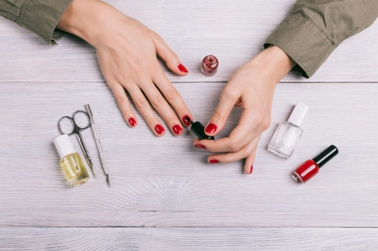 Top view of a woman doing a manicure and paint nails with red lacquer