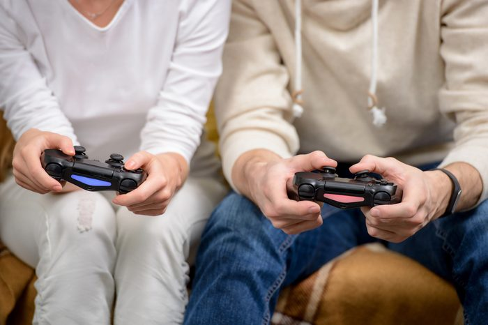 Close up photo of young friends playing video games in living room. Focus on hands and controllers
