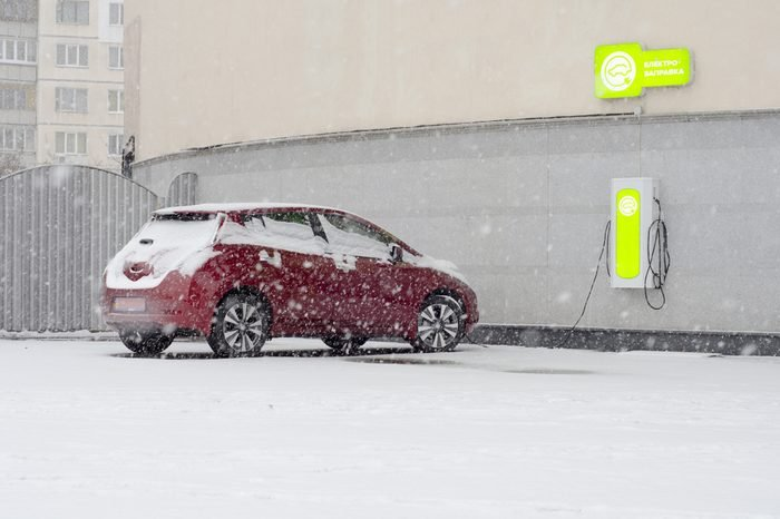 Electric car at charging in winter