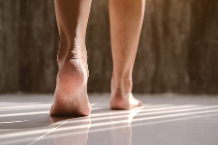 Female feet walking on floor brick room with sunlight
