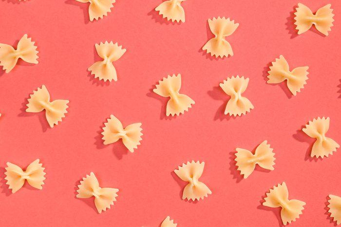 Farfalle pasta random flat lay pattern on red background