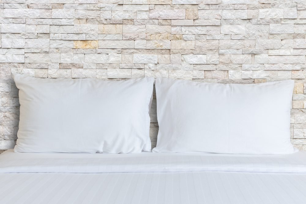Close up white bedding sheets and pillow in hotel room.