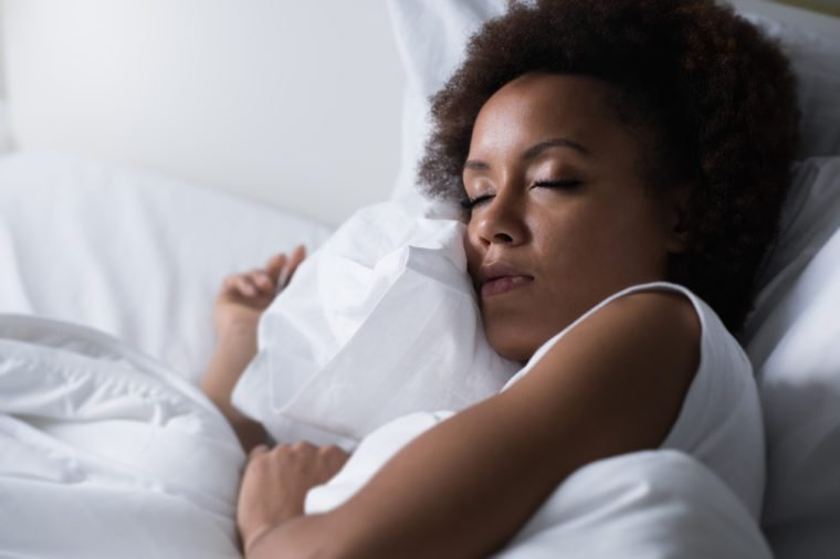 Young african woman sleeping in her bed at night, she is resting with eyes closed