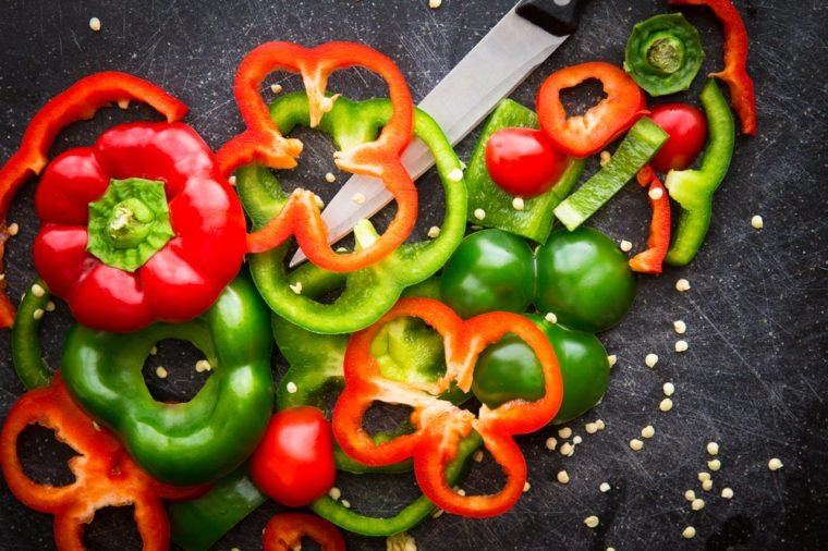 Cutting board and knife with fresh organic red and green bell peppers sliced and chopped for meal preparation.