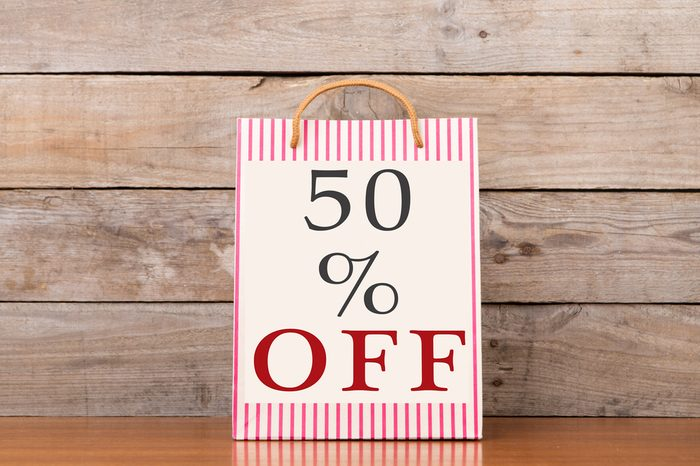 """Shopping bags with inscription """"50% OFF"""" on wooden background"""