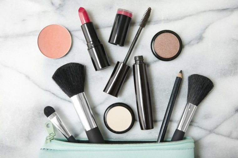 Overhead view of make up products spilling out of a pastel blue cosmetics bag, on a white marble counter top background