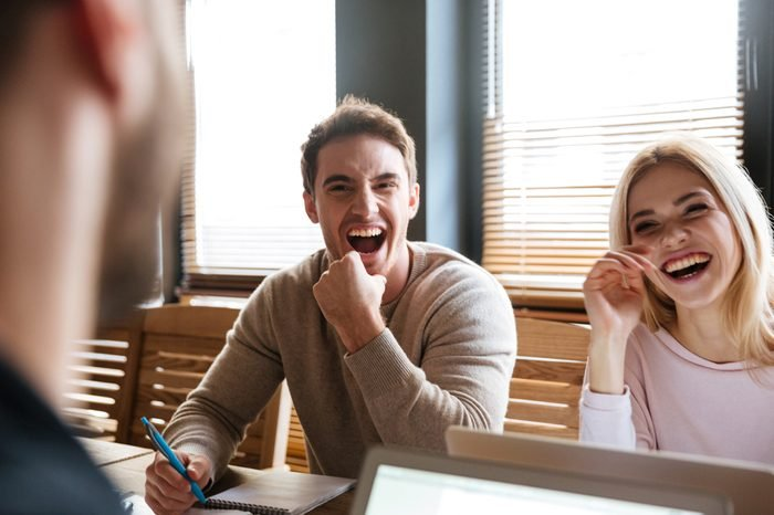 Photo of three young laughing colleagues sitting near coffee while work with laptops and notebook. Coworking.