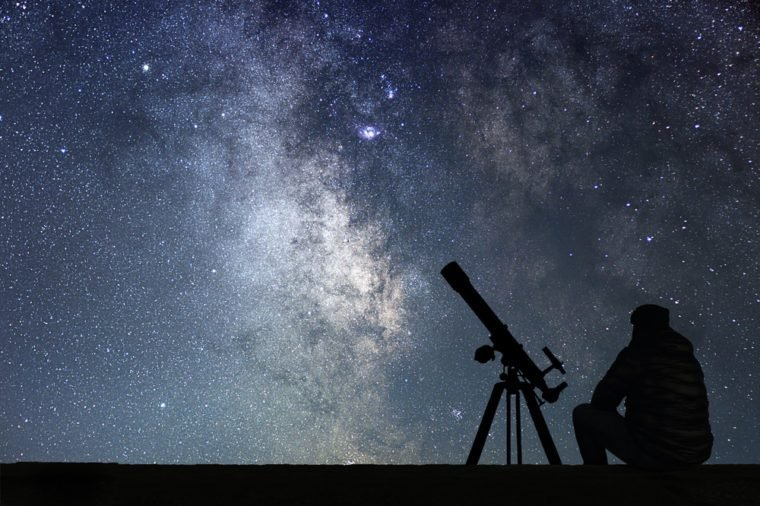 Man with astronomy telescope looking at the stars. Man telescope and starry sky. Night sky. Milky way galaxy.