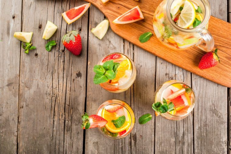 Traditional summer drink white sparkling sangria. With champagne, strawberries, oranges, lemon, green apple and grapefruit. On a wooden rustic table, with a jug and ingredients. Copy space top view