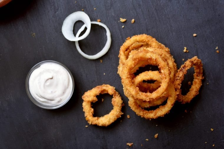 Crunchy fried onion rings and white sauce on dark background, top view