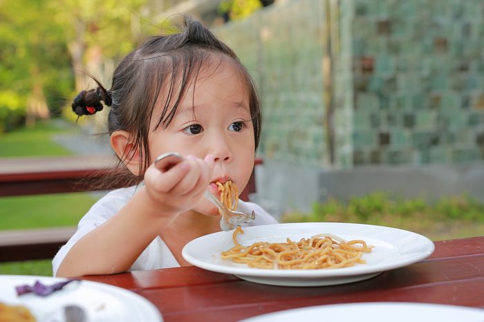 Kid girl eating Japanese yakisoba noodles