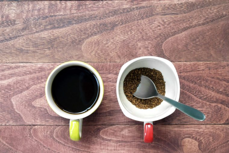 black coffee and instant coffee with silver spoon in coffee cup on brown wooden table floor, close up top view two cups