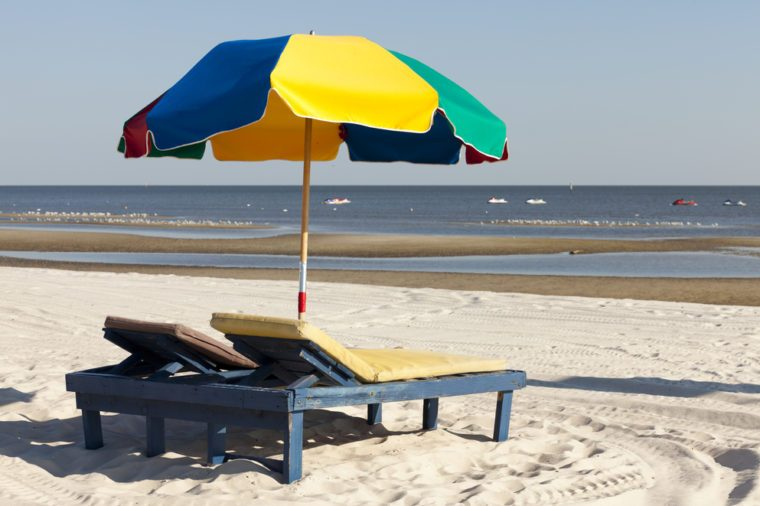 Colorful beach lounge chairs and umbrella along the Mississsippi Gulf Coast.