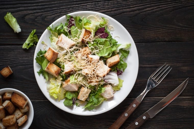 Fresh caesar salad in white plate on dark wooden table. Top view.