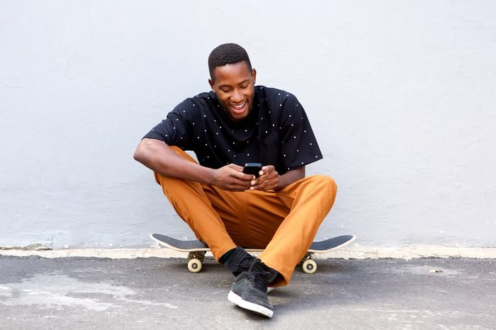 Portrait of attractive young african man sitting with skateboard and using smart phone