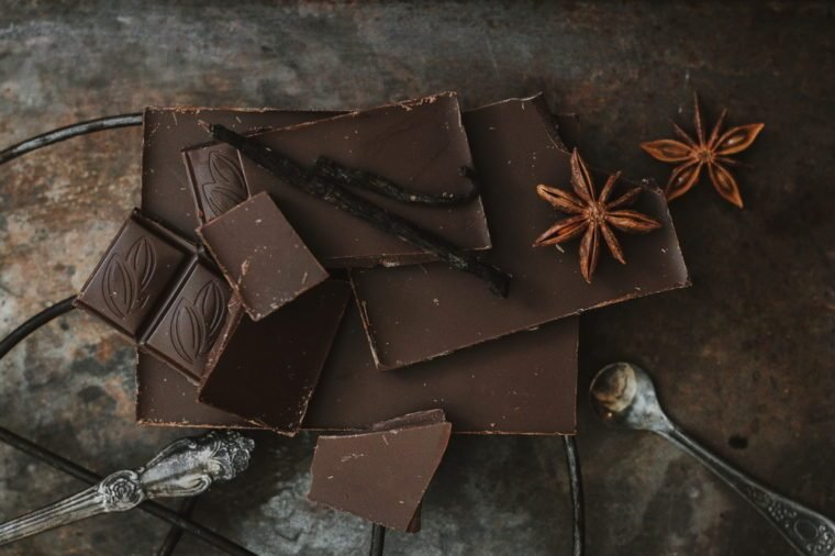 Top view. Chocolate bar. Dark chocolate on a dark background with spices. Anise.
