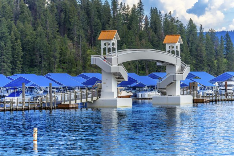 COEUR D'ALENE, IDAHO - MAY 19, 2017 Walking Bridge Blue Covers Boardwalk Marina Piers Boats Reflection Lake Coeur d' Alene Idaho