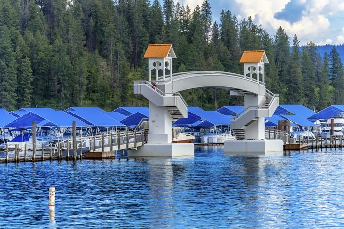 COEUR D'ALENE, IDAHO - MAY 19, 2017 Walking Bridge Blue Covers Boardwalk Marina Piers Boats Reflection Lake Coeur d' Alene Idaho
