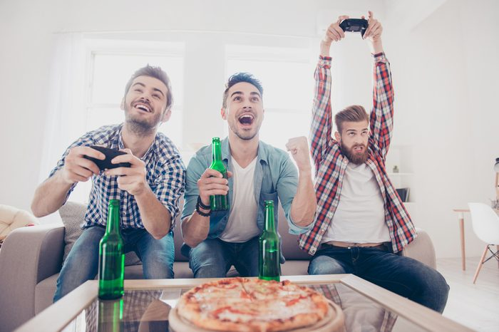 Crazy, fun, joy, winners and looser! Young men are sitting on couch and playing video games indoors at home with beer and pizza, expressing emotions and feelings, gesturing