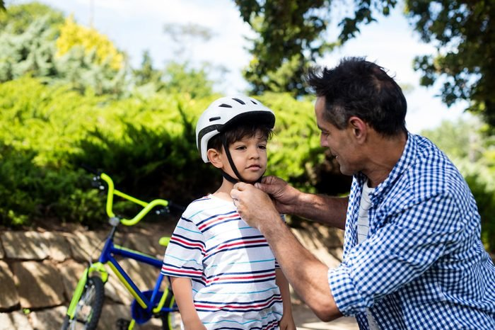 Father assisting son in wearing bicycle helmet in park on a sunny day