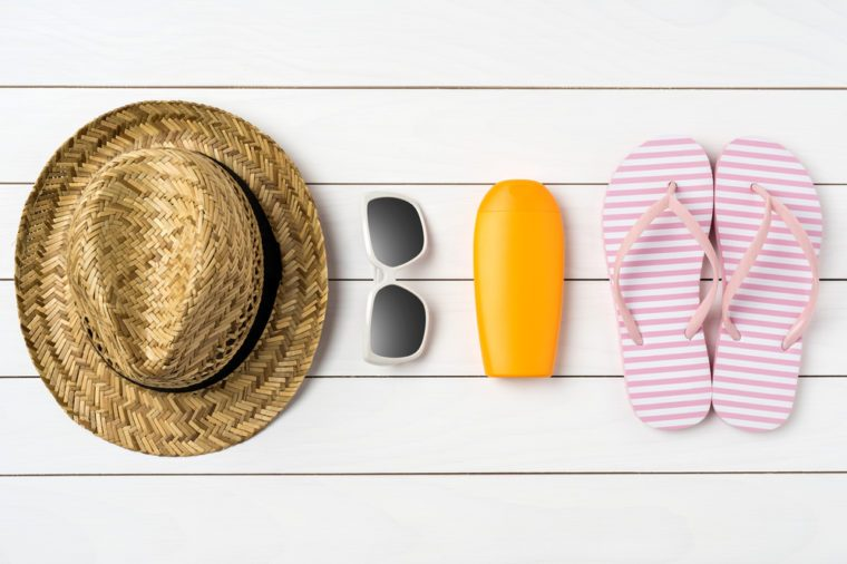 Summer background with straw hat, sunglasses, sunscreen bottle and pink flip flops