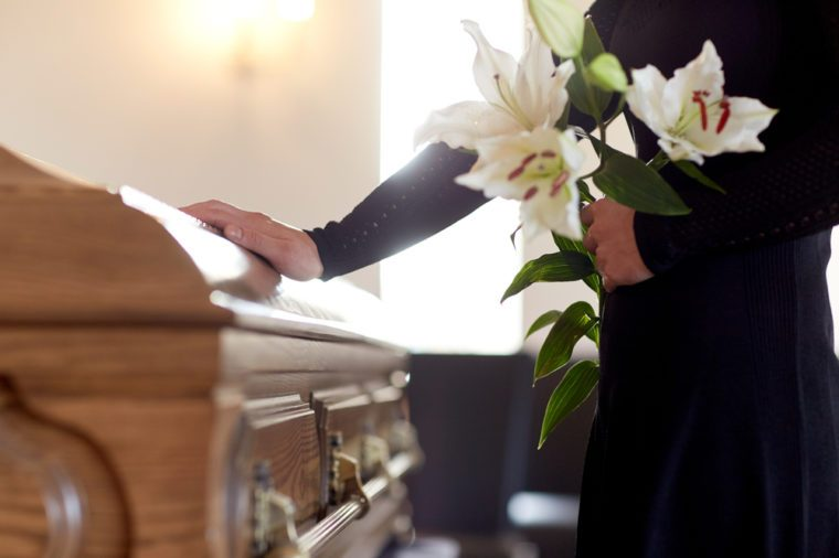 people and mourning concept - woman with white lily flowers and coffin at funeral in church