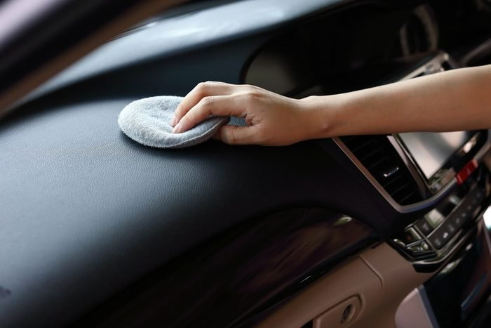 woman hand cleaning leather black console in car with soft fabric sponge waxing polished