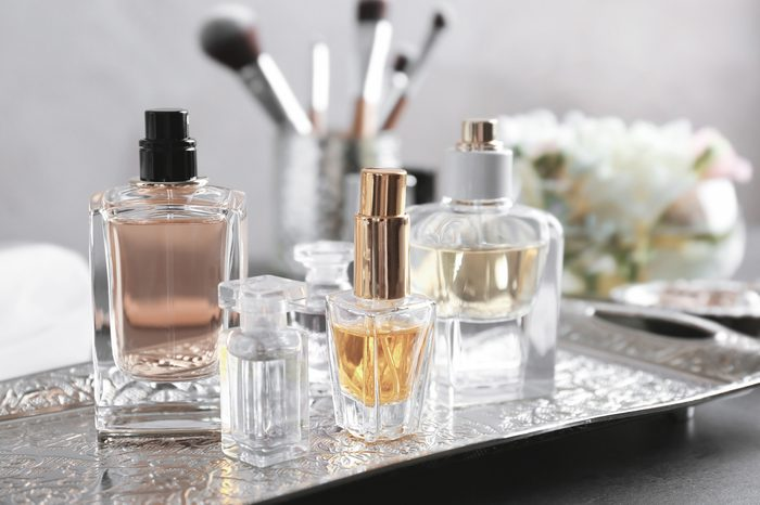 Metal tray with bottles of perfume on table