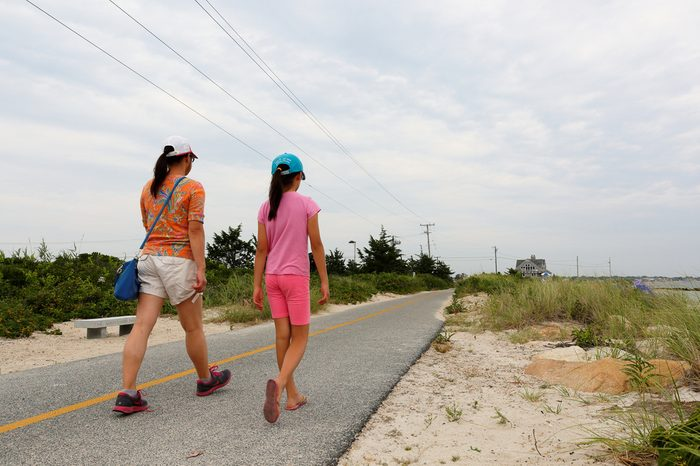 Cape Cod, Massachusetts - July 22, 2017: People walking on the Shining Sea Bikeway on Cape Cod, Massachusetts. The bikeway is about 10 miles long along the coast line of Cape Cod.