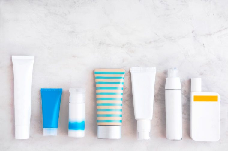 Skincare cosmetic products from above on white marble table. Cream, cleancer, bb, cc foundation, sunscreen, moisturizer, lotion. Branding mock up. Copyspace