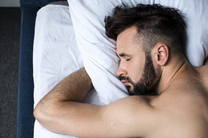 close-up view of handsome young bearded man sleeping in bed at home