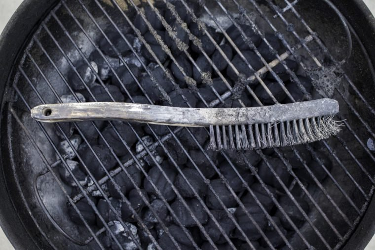 Grill brush resting on a dirty grill.