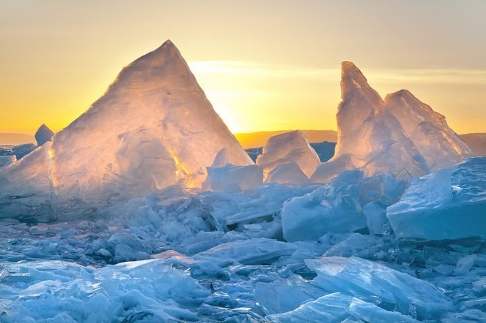 Lake Baikal in Siberia at sunset, lots of beautiful pieces of ice and hummocks with reflection. The natural background.