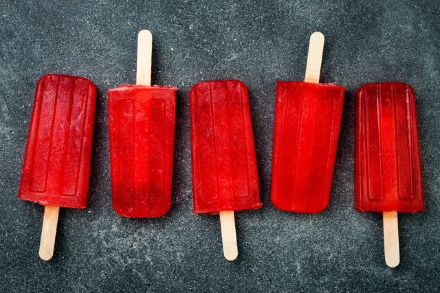 Homemade frozen blood orange natural juice alcoholic popsicles - paletas - ice pops. Overhead, flat lay, top view. Halloween party recipe idea