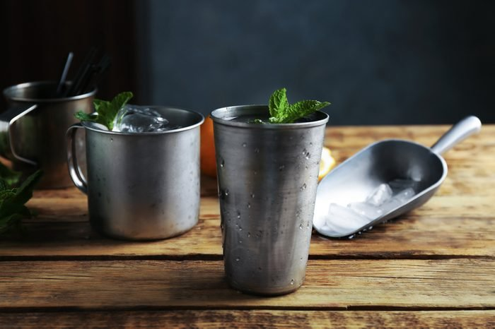 Metal glass with mint julep on kitchen table