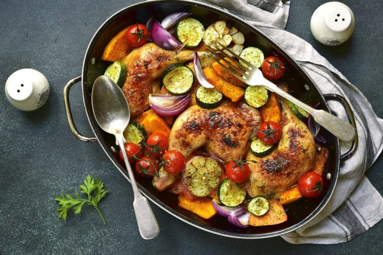 Chicken legs roasted with vegetables in a skillet pan over dark slate,stone or concrete background.Top view.