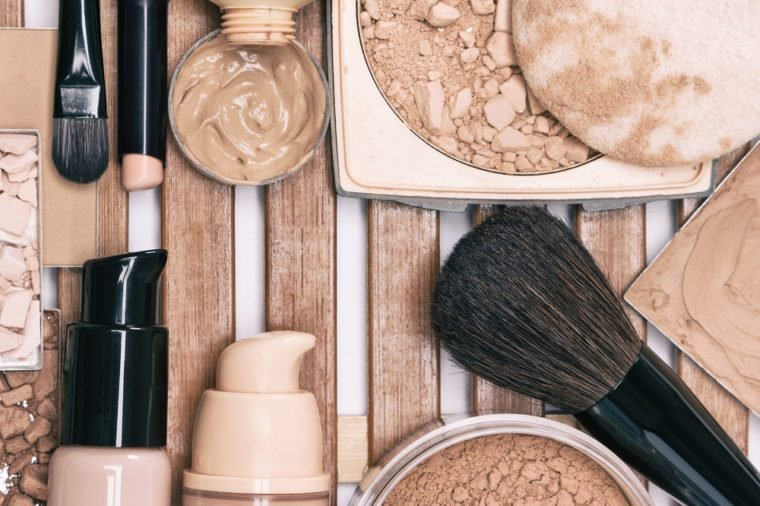 Makeup products for flawless complexion: concealer, foundation, powder with professional make-up brushes