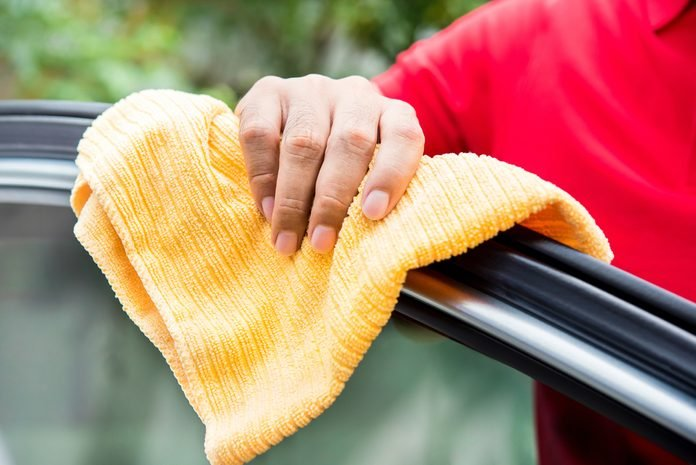 Male auto care service staff cleaning car window with microfiber cloth